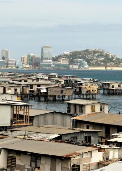 """Stilt Houses Port Moresby"" by gailhampshire is licensed under CC BY 2.0. To view a copy of this license, visit https://creativecommons.org/licenses/by/2.0/"